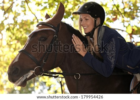 Closeup photo of attractive female rider leaning over horse, smiling happy. - stock photo