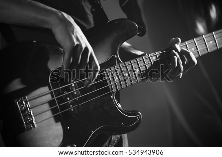 Closeup photo of bass guitar player hands, soft selective focus, live music theme, black and white