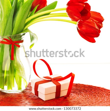 Closeup photo of beautiful romantic still life isolated on white background, fresh red tulips bouquet, small white present with ribbon decoration, happy mothers day, love and romance concept - stock photo