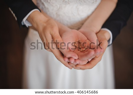 Closeup photo of bride and groom holding golden wedding rings on hands no face  - stock photo