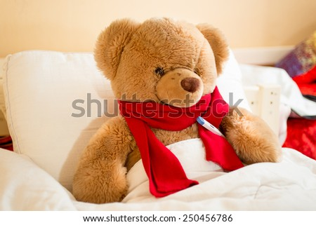 Closeup photo of brown teddy bear in read scarf lying in bed with thermometer - stock photo