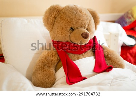 Closeup photo of brown teddy bear in red scarf lying in bed - stock photo