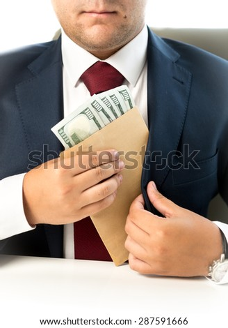 Closeup photo of businessman hiding envelope with money in pocket at jacket