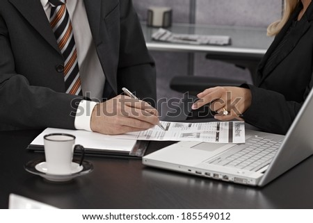 Closeup photo of businesspeople discussing diagrams and charts. Only arms hands, laptop business report and coffee cup can be seen. - stock photo