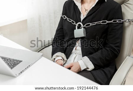 Closeup photo of businesswoman tied to chair by metal chain - stock photo