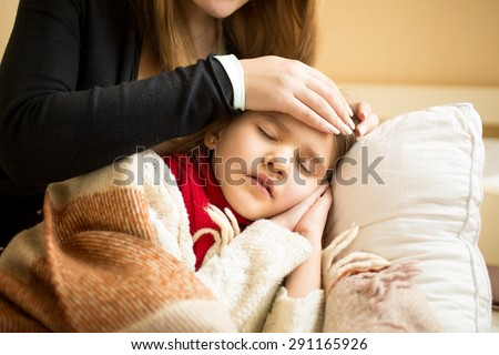 Closeup photo of caring mother holding head on sick daughter forehead - stock photo