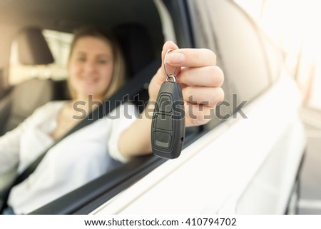 Closeup photo of cheerful young woman driving car and showing car keys - stock photo