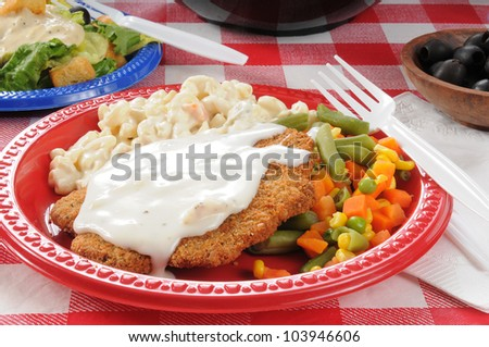 Closeup photo of chicken fried steak on a picnic table with country gravy and macaroni salad