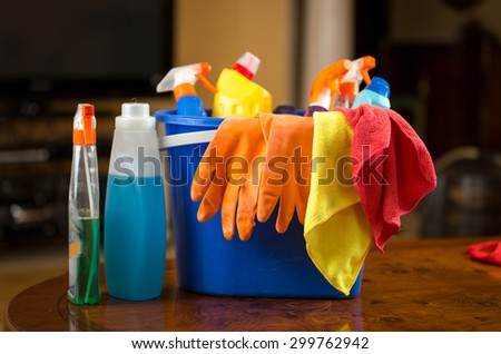 Closeup photo of cleaning chemicals, gloves and rags lying in plastic bucket - stock photo