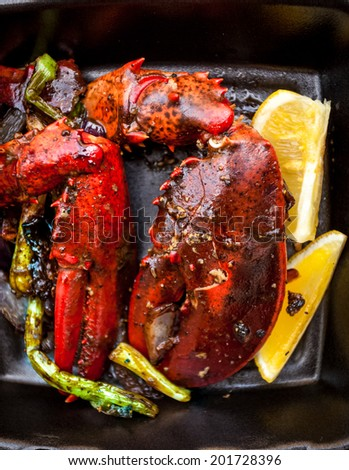 Closeup photo of cooked lobster claw with lemon and vegetables - stock photo