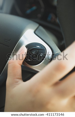 Closeup photo of driver using control panel on steering wheel - stock photo