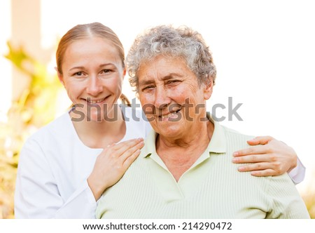 Closeup photo of elderly woman with the caretaker  - stock photo
