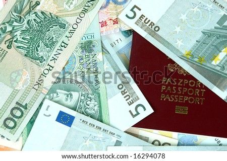 Closeup photo of European passport cover with different banknotes from Europe, China, Poland and Hongkong.