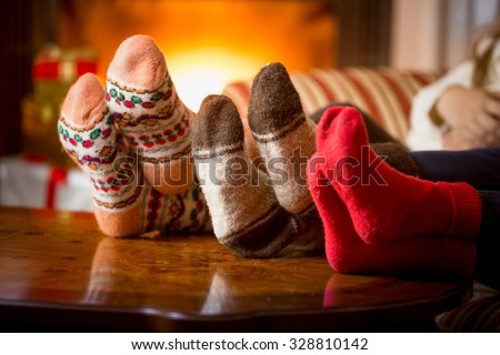 Closeup photo of family feet in wool socks at fireplace - stock photo