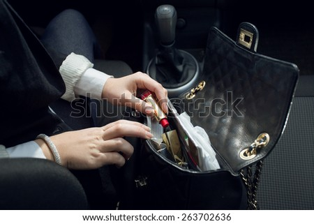 Closeup photo of female driver searching for lipstick in purse - stock photo