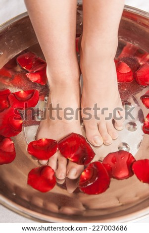 Closeup photo of female feet at spa salon on pedicure procedure. Female legs in water decoration flowers.  - stock photo