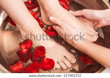 Closeup photo of female feet at spa salon on pedicure procedure. Female legs in water decoration flowers and getting massage - stock photo