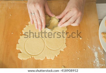 Closeup photo of female hands cutting dough for cookies - stock photo
