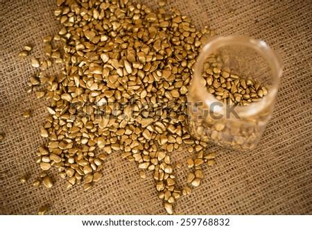 Closeup photo of golden nuggets and empty bullion lying on burlap - stock photo