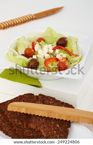 Closeup photo of healthy food. Fresh green salad and brown bread on white tabletop. - stock photo