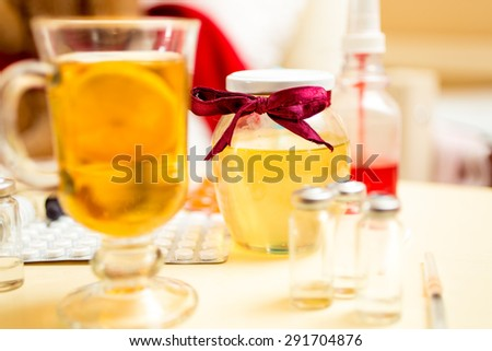 Closeup photo of hot tea, honey jar and pills on bedside table - stock photo