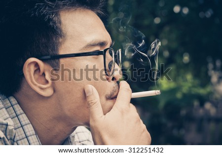 Closeup photo of man hold a smoking in outdoor and wearing a spectacles. disease lung risk stress loneliness chronic - stock photo