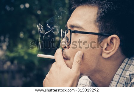 Closeup photo of man hold a smoking in outdoor and wearing a spectacles : The dangers of smoking : The source of lung disease : Vintage tone of man a smoking - stock photo