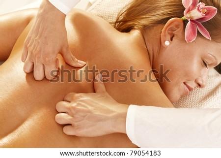 Closeup photo of masseur's hands doing deep tissue massage.? - stock photo