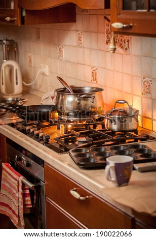 Closeup photo of metal pan boiling on burning gas stove on country style kitchen - stock photo