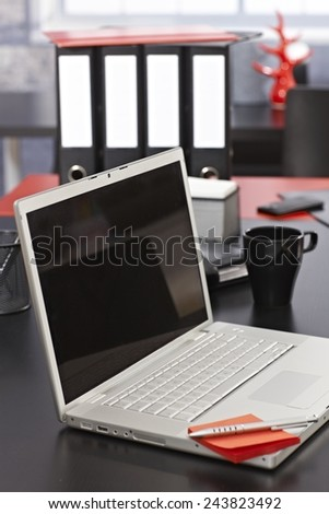 Closeup photo of office desk with laptop and folders, pen and paper. - stock photo