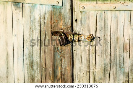 Closeup photo of old metal lock hanging on wooden barn door - stock photo