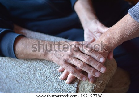 Closeup photo of old people holding hands