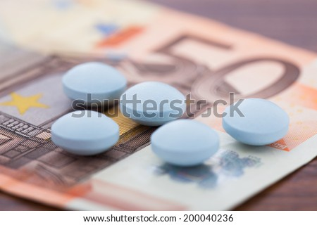 Closeup photo of pills lying on euro banknote - stock photo