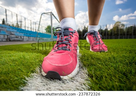 Closeup photo of pink female sneakers on soccer grass field - stock photo