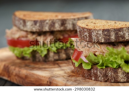 closeup photo of sandwich with tuna and vegetables on rye bread on wood background - stock photo