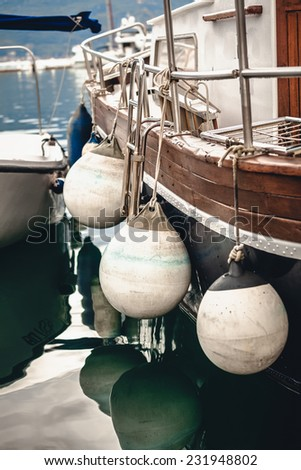 Closeup photo of side of the ship with big white buoys - stock photo