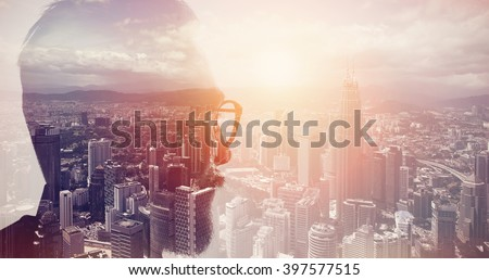 Closeup photo of stylish bearded banker wearing glasses and looking city. Double exposure, panoramic view contemporary megalopolis background. Space for your business message. Wide, sunset effect
