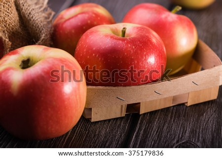 Closeup photo of tasty ripe juicy smooth red yellow apples in small crate box with burlap on grey wooden table, horizontal picture  - stock photo