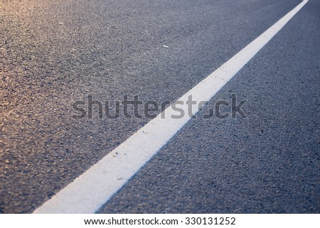 Closeup photo of the road with white line. - stock photo