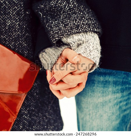Closeup photo of two hands of young couple in love in winter cold weather stylish hipster clothing