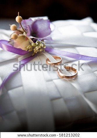 Closeup photo of two wedding rings lying on satin cushion decorated with flowers - stock photo