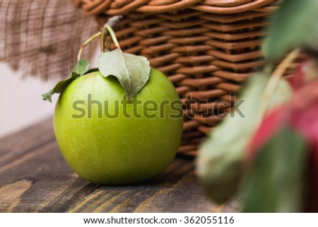 Closeup photo of whole fresh ripe juicy green apple with smooth peel and leaves on shank near basket with burlap on brown wooden table, horizontal photo - stock photo