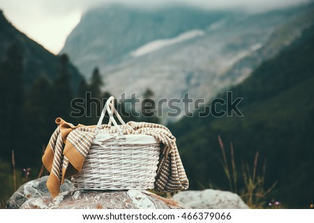Closeup photo of wicker basket with blanket over mountains view, picnic in cold season