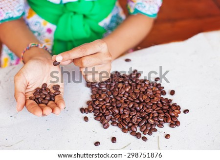 Closeup photo of woman choosing the coffee beans of the best quality  - stock photo