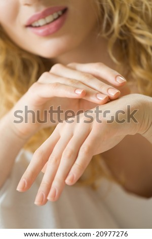 Closeup photo of woman hands applying creme - stock photo
