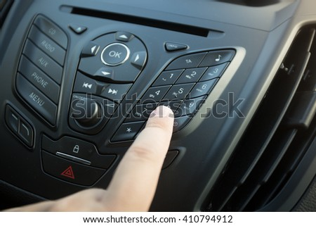 Closeup photo of woman pressing button on car dashboard