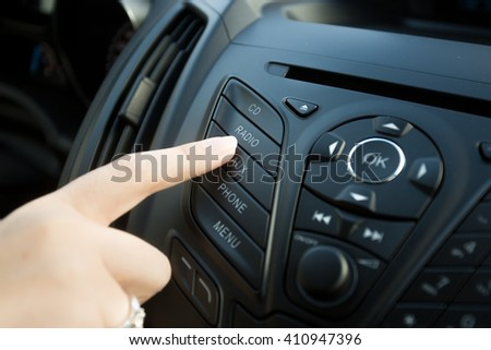 Closeup photo of woman pressing radio button on car dashboard