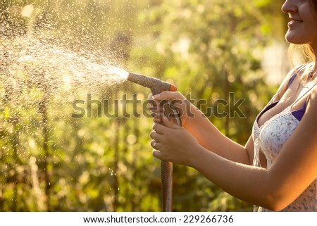 Closeup photo of woman watering garden with hosepipe at hot sunny day - stock photo