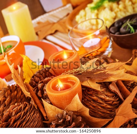 Closeup photo on beautiful autumnal still life for Thanksgiving day, pine cone and dry leaves decoration for festive dinner - stock photo