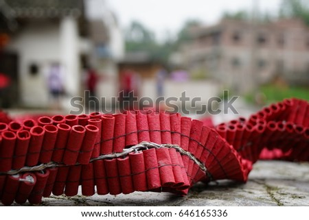 Closeup photos of a red rocket firecrackers were places on the ground with the blurred background of Chinese home.